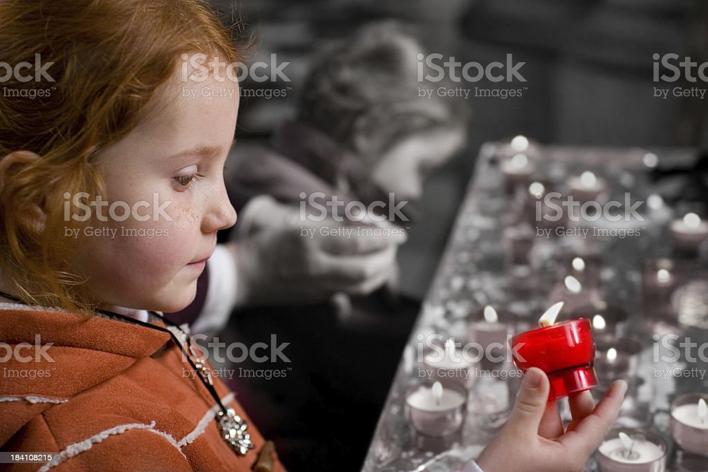 Young girl in church, lighting a candle royalty-free stock photo