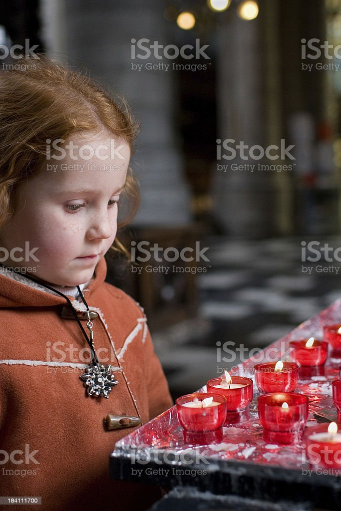 Young girl in church with candles royalty-free stock photo