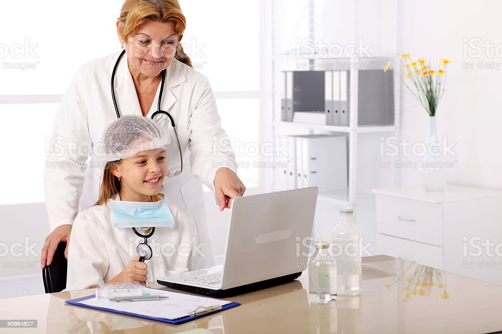 Young girl in doctor's uniform looking on the laptop. royalty-free stock photo