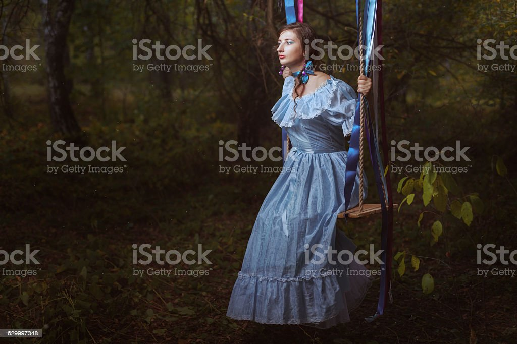 Young girl in fairy forest on a swing. stock photo