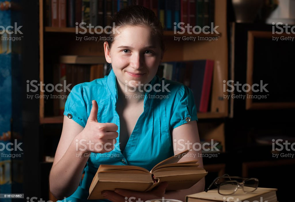 young girl in glasses reading a book stock photo