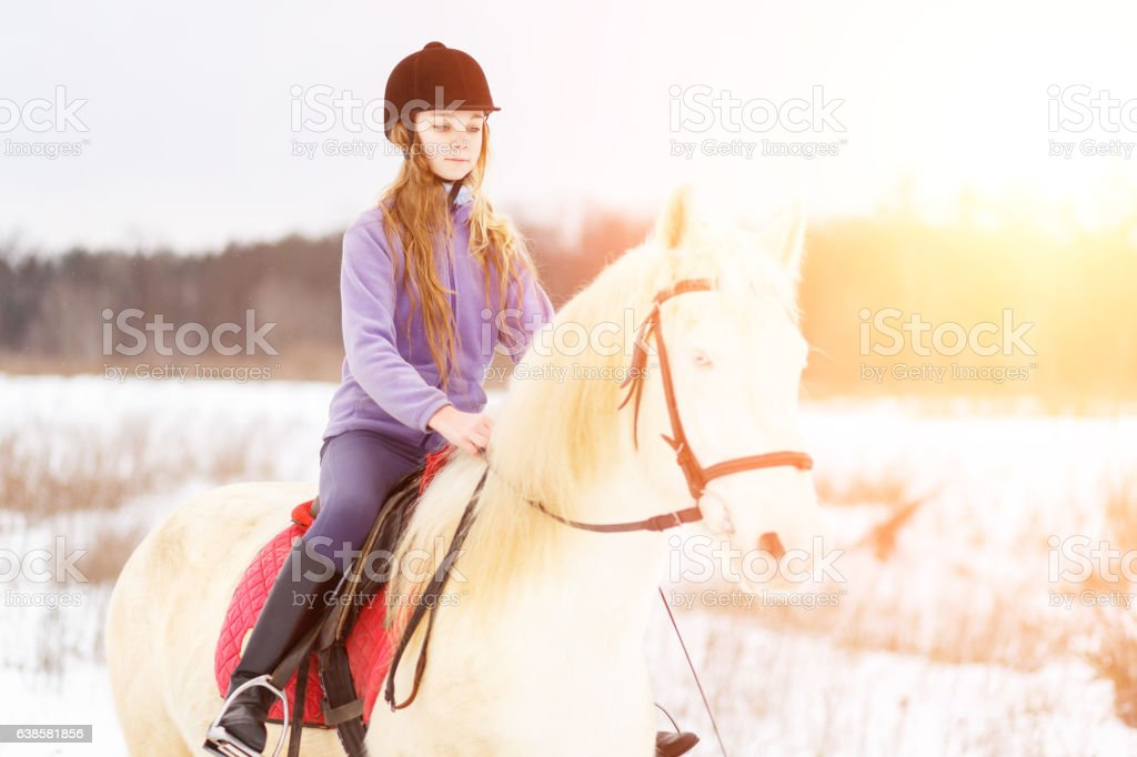 Young girl in helmet riding white horse on field stock photo