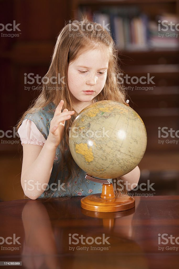 Young girl in home setting looking at a globe royalty-free stock photo