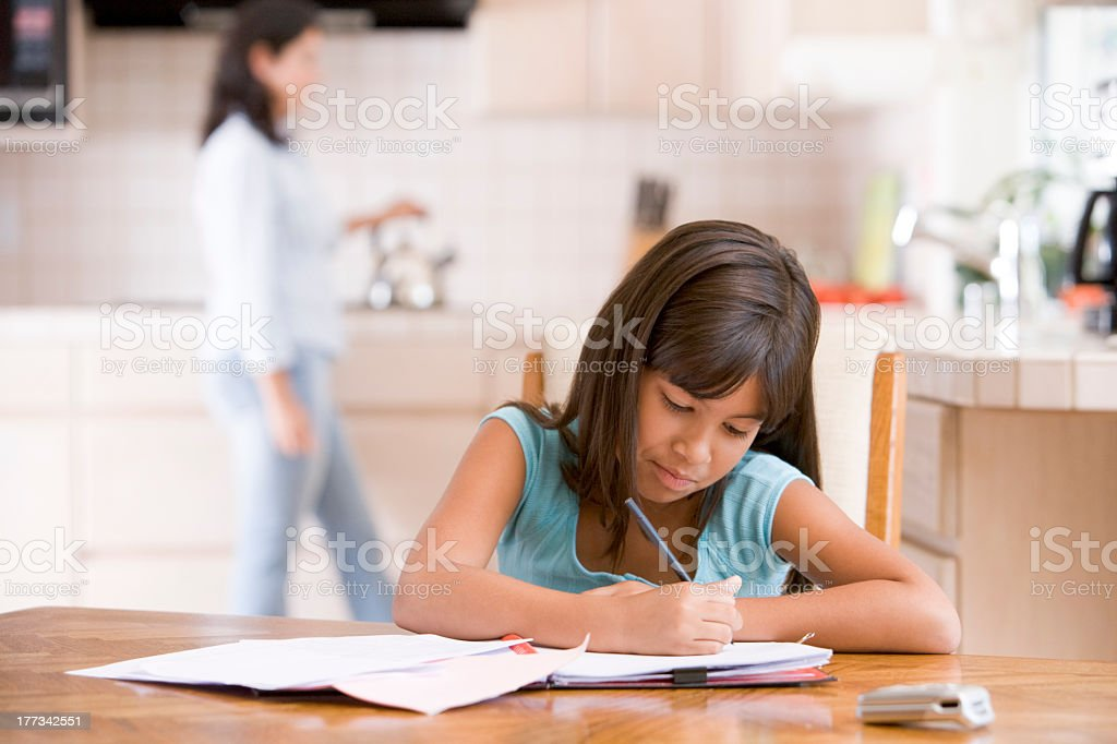 Young girl in kitchen doing homework stock photo