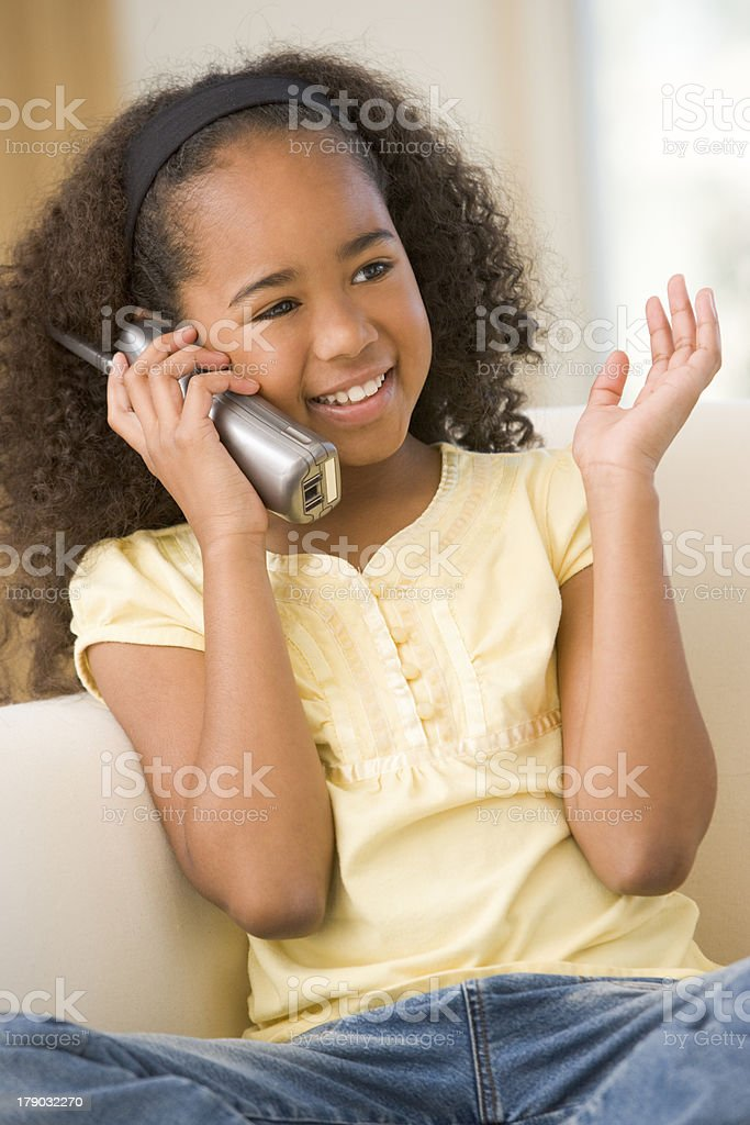 Young girl in living room using telephone and smiling stock photo