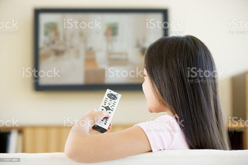 Young girl in living room with television and remote control stock photo