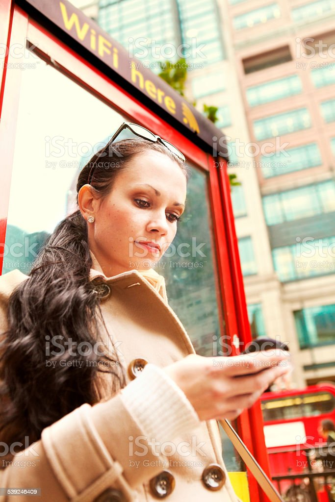 Young girl in London connected with phone to to wifi stock photo