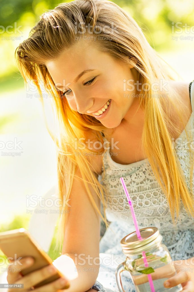 Young girl in nature with mobile phone stock photo