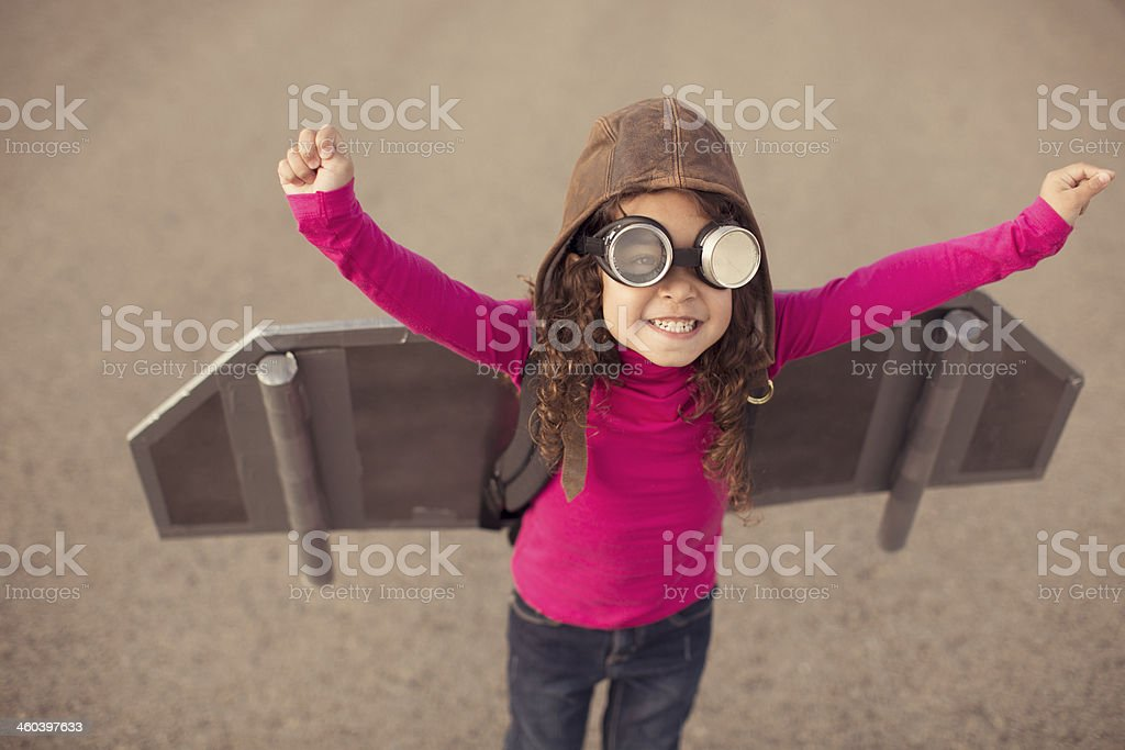 Young girl in pilot gear with toy aircraft wings stock photo