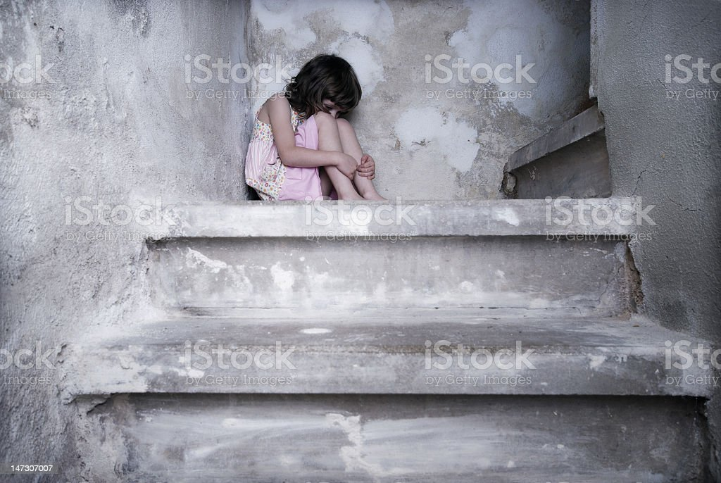 A young girl in pink cowering at the top of the stairs royalty-free stock photo