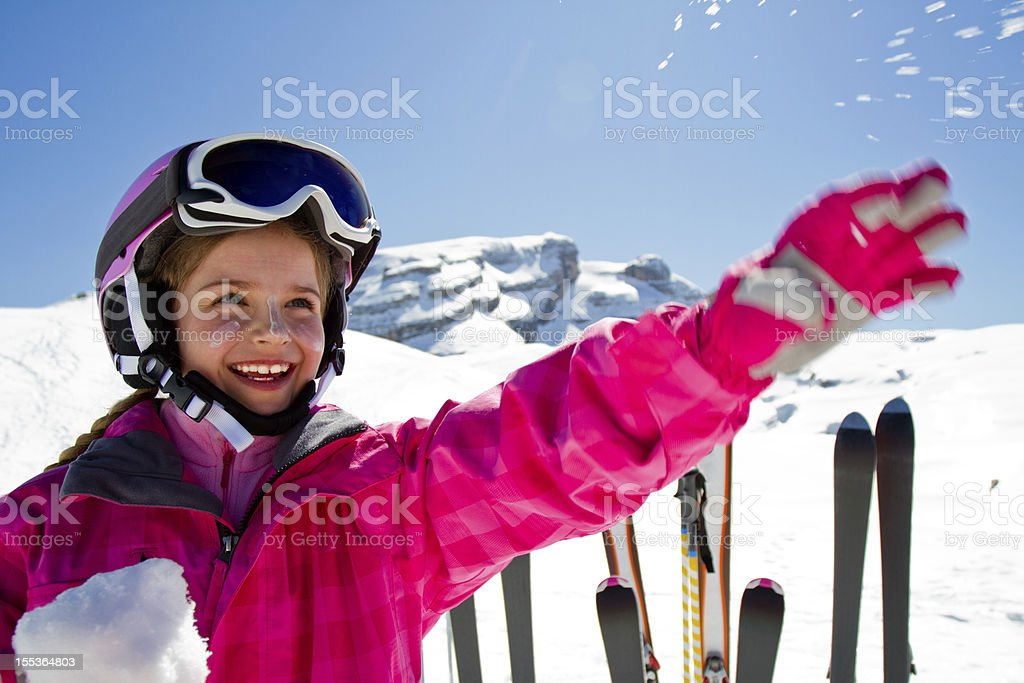 Young girl in pink playing in the snow on a ski slope stock photo