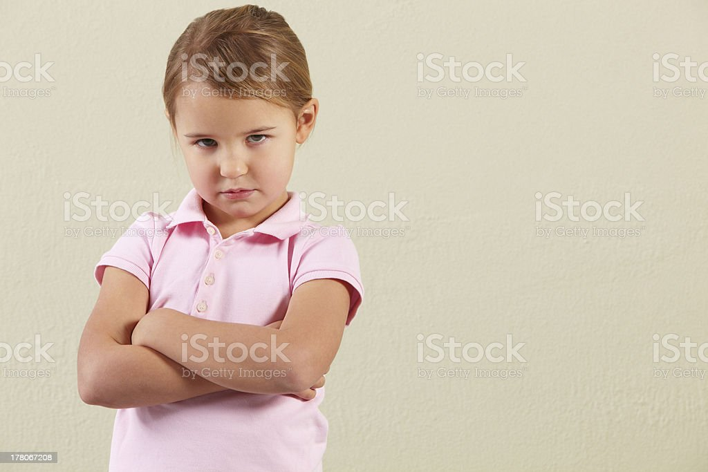 Studio Shot Of Angry Young Girl Looking At Camera Standing Still