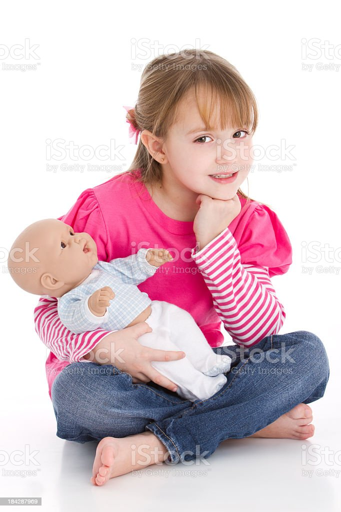 Sweet little girl as a mom playing with a baby doll