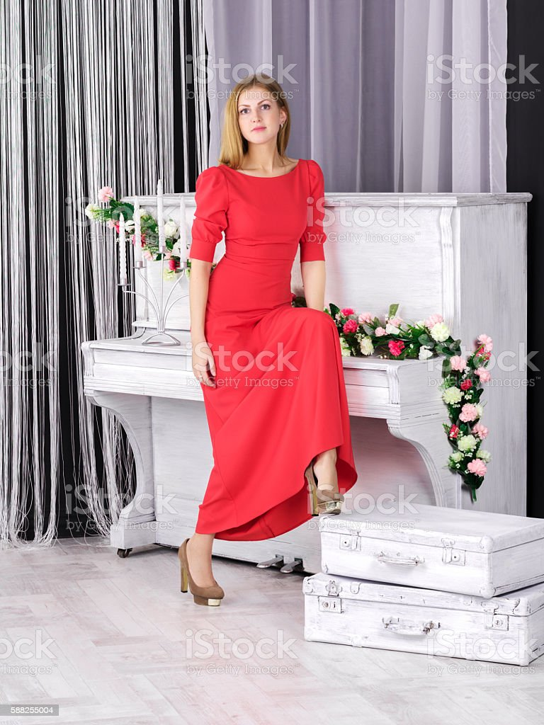 Young girl in red dress standing near piano stock photo