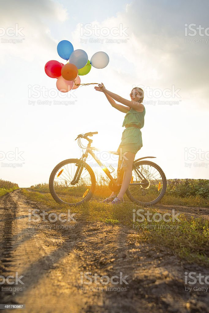 Young Girl in sexy dress with sunglasses riding bicycle flying stock photo