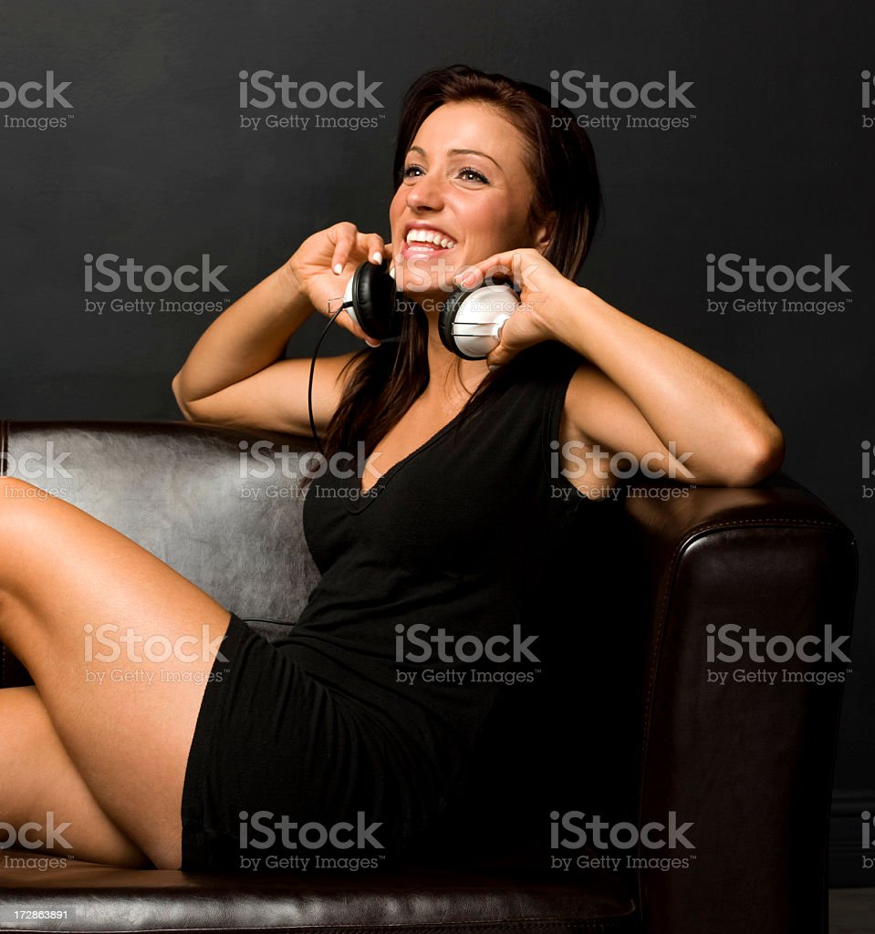Young girl in short black dress with white earphones. stock photo