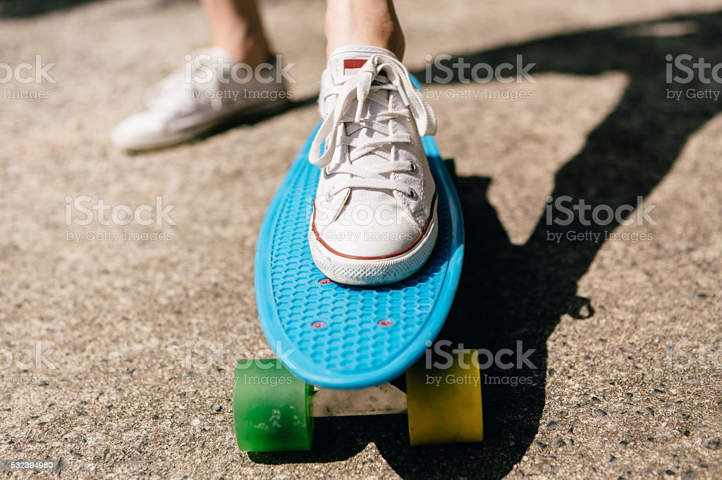 Young girl in sneakers on skateboard. stock photo