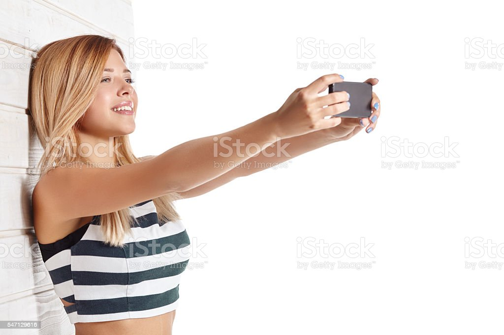 Young girl in striped top makes selfie stock photo