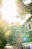 Young girl in sundress running in bright garden, candid portrait