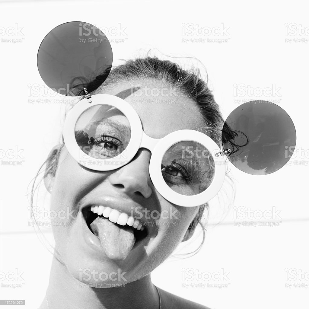 young girl  in sunglasses showing tongue stock photo
