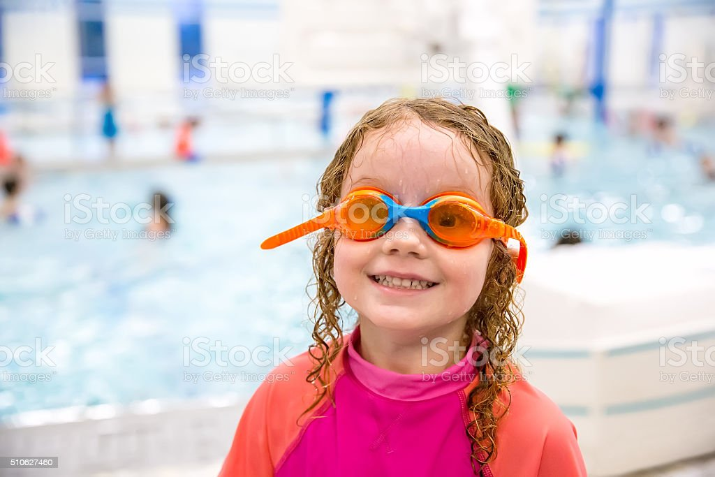 Young Girl in Swim Goggles At Indoor Swimming Pool stock photo