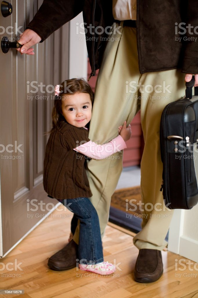 young girl in the doorway hugging her dads leg stock photo