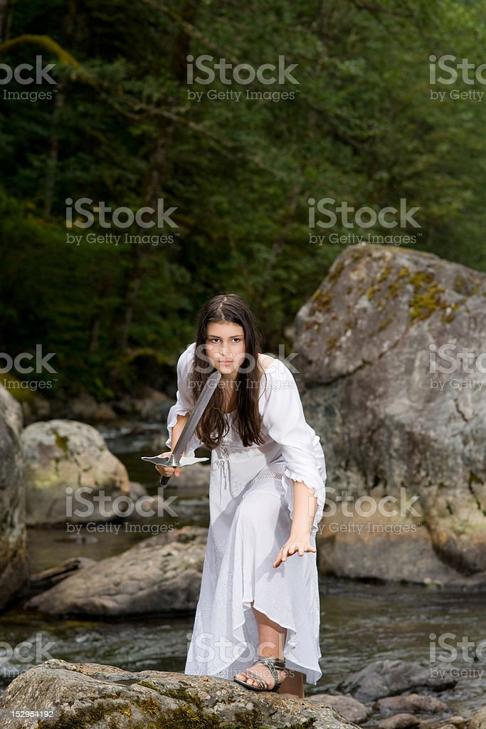 Young girl in white dress with two handed sword stock photo