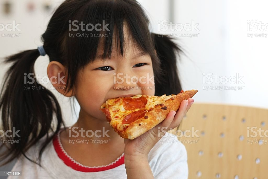 Young girl in white shirt eating pizza stock photo