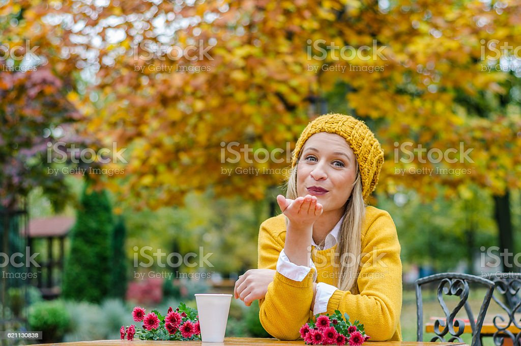 Young girl in yellow clothes sends a kiss stock photo