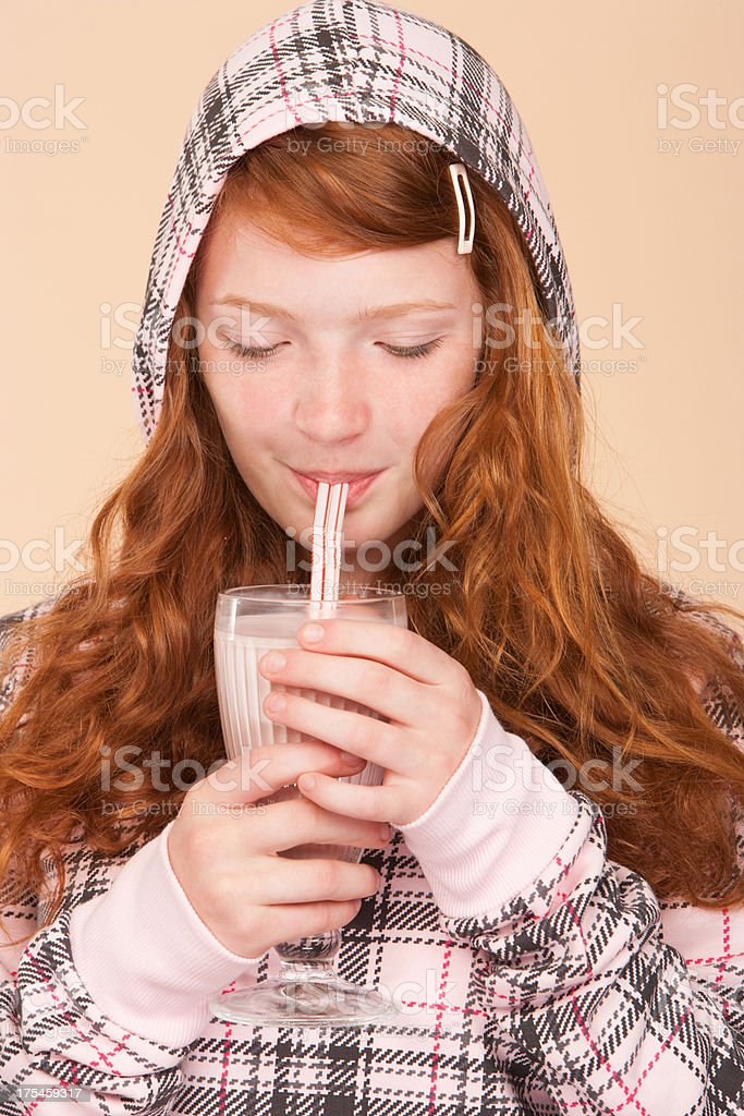 Young girl indoors drinking strawberry milk shake royalty-free stock photo