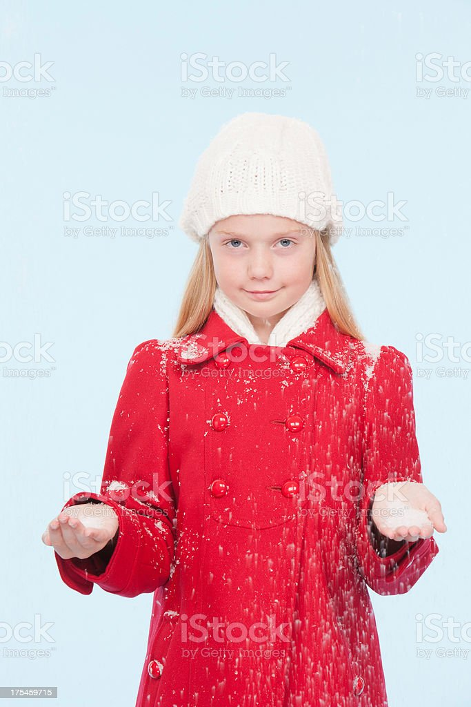 Young girl indoors holding snow in hands stock photo