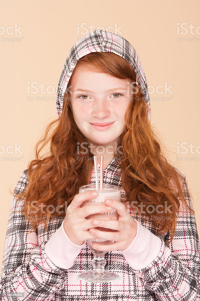 Young girl indoors holding strawberry milk shake royalty-free stock photo