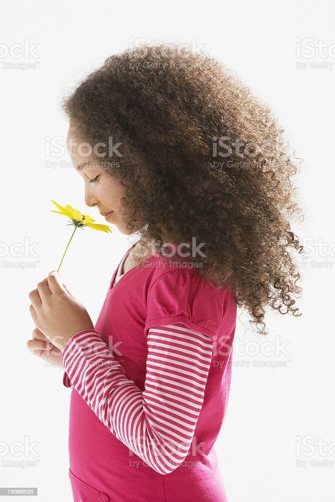 Young girl indoors smelling a flower royalty-free stock photo