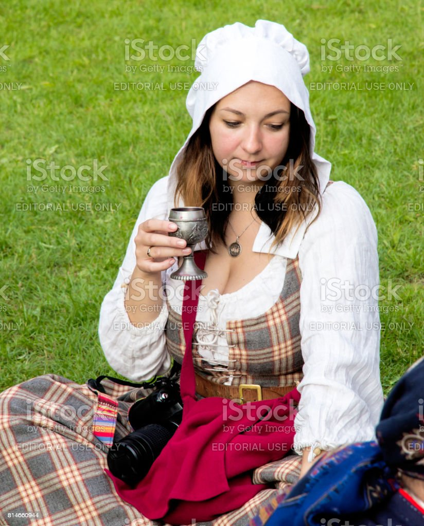 Young girl, iron cup in hand sits on the grass. stock photo