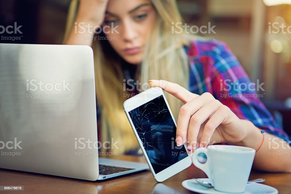 Young girl is devastated after her mobile phone is fall down. stock photo