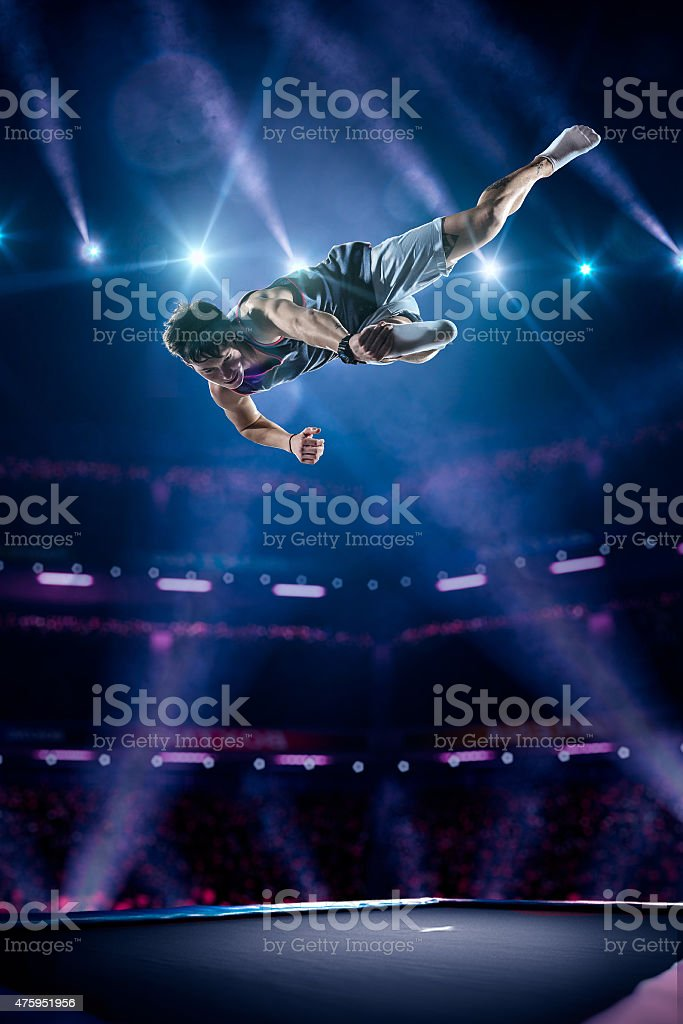 Young girl is jumping on trampoline stock photo