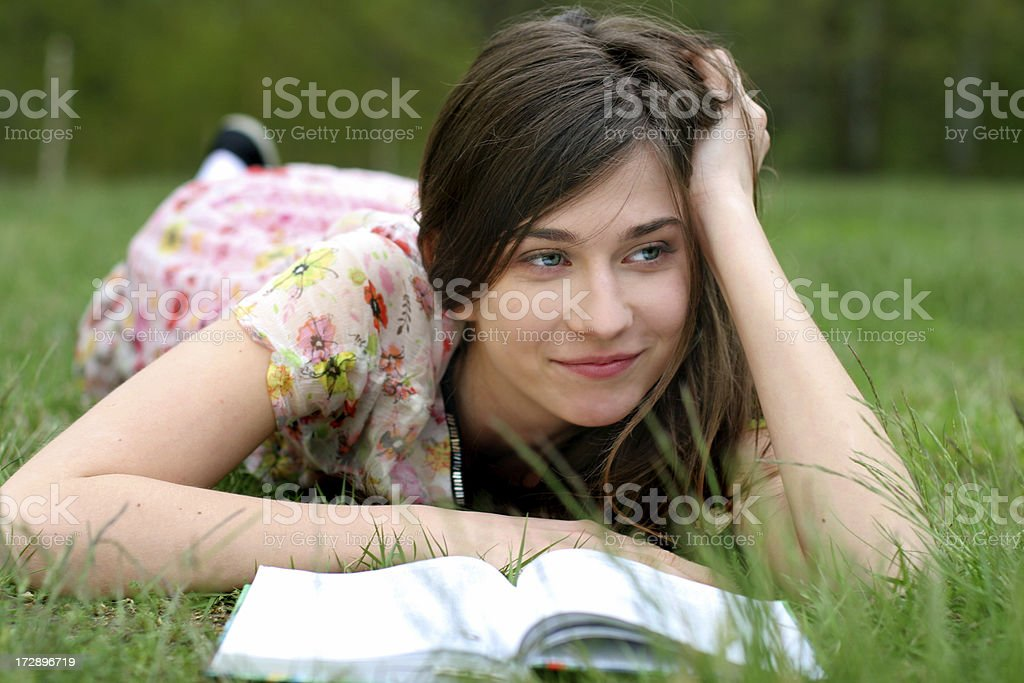 young girl is laying on the grass with a book royalty-free stock photo