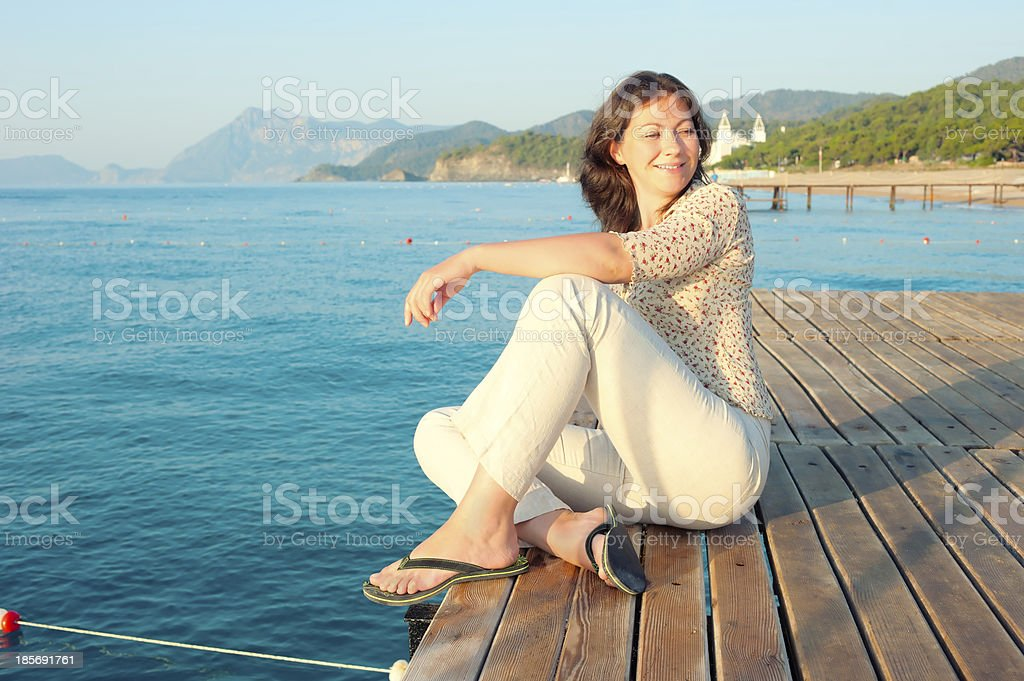 Young girl is resting on  wooden pier near the sea royalty-free stock photo