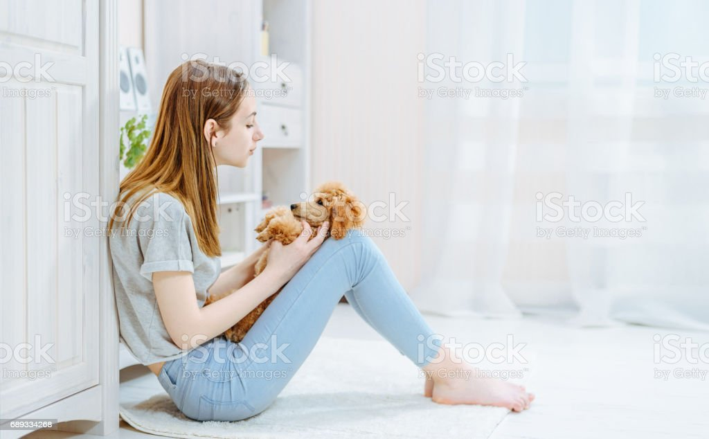 Young girl is resting with a dog on the floor at home . stock photo