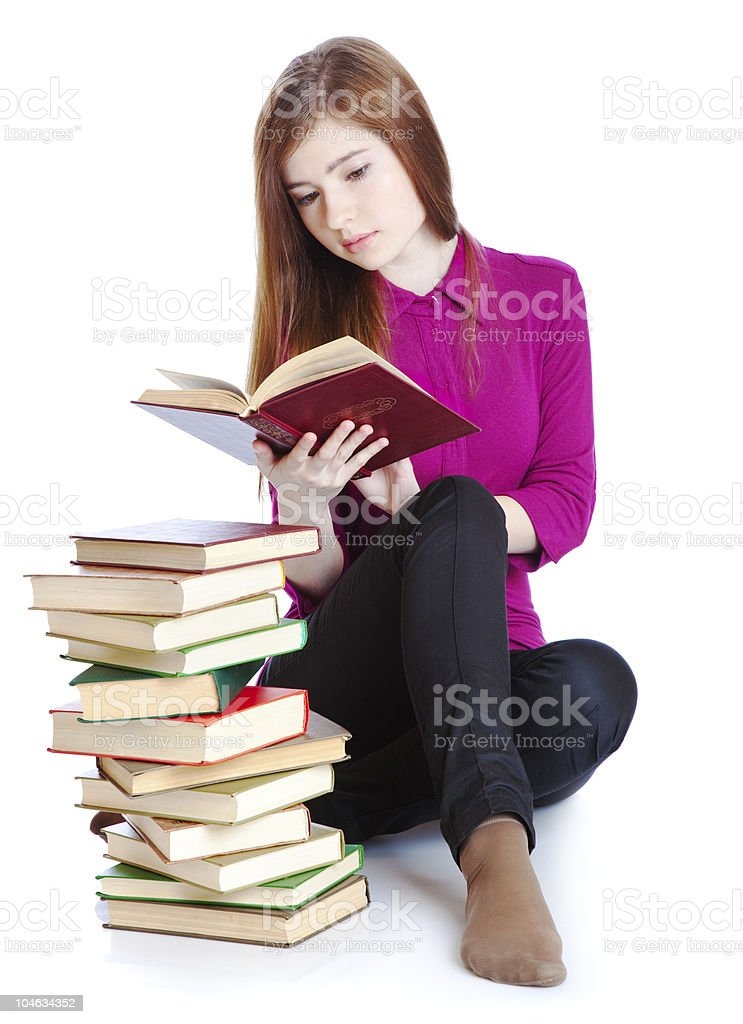 Young girl is sitting on a floor and reading book royalty-free stock photo