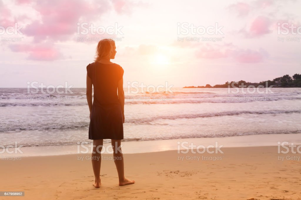 Young girl is standing at sunset sea beach and dreaming or thinking about something. stock photo