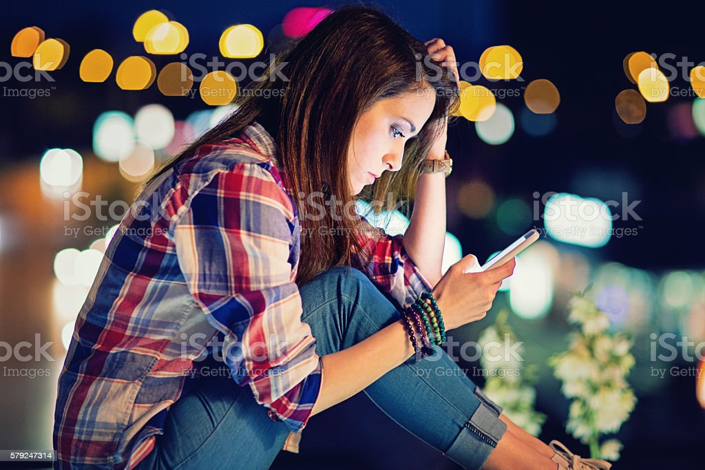 Young girl is standing sad on the bridge stock photo