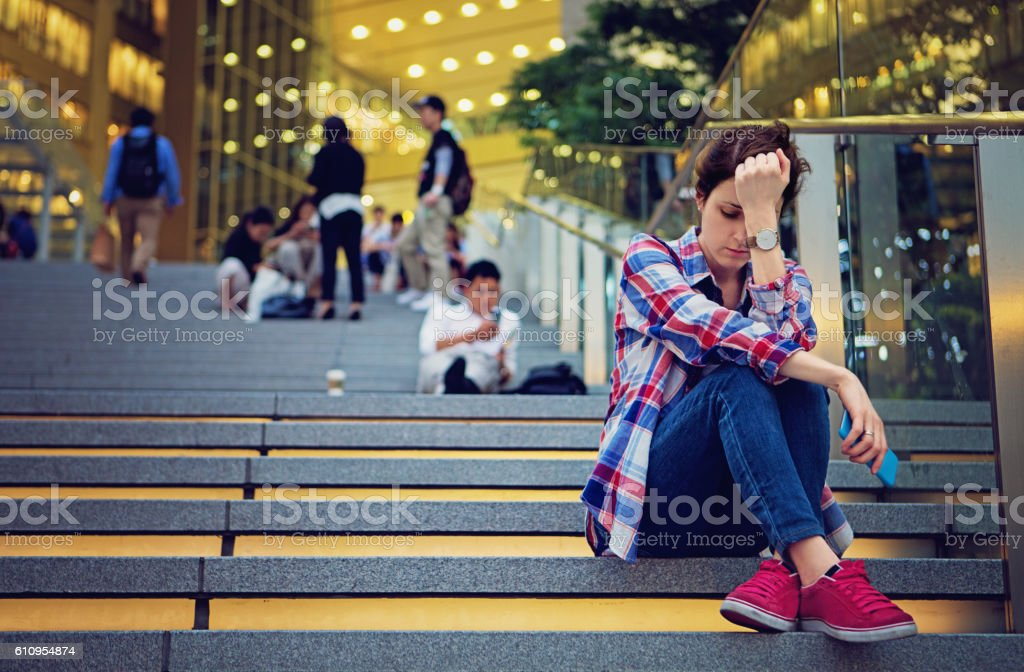 Young girl is standing sad on the stairs stock photo
