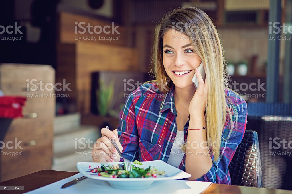 Young girl is talking using her mobile phone in restaurant stock photo