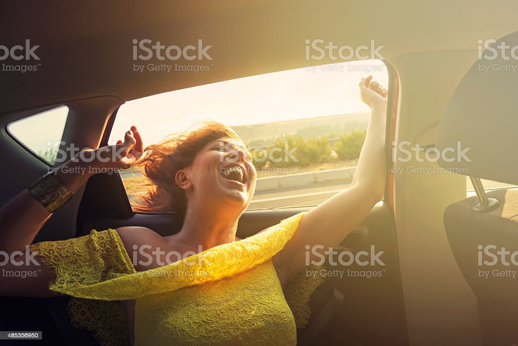 Young girl is travelling in a car on a sunny day stock photo