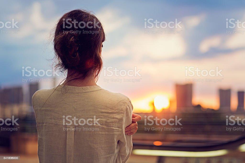 Menina está a assistir pôr do sol ao longo de Tóquio - fotografia de stock