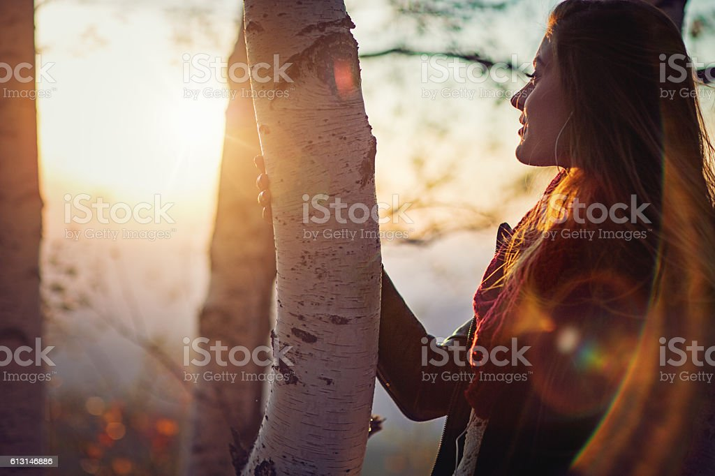 Young girl is watching the sunset in mountain stock photo
