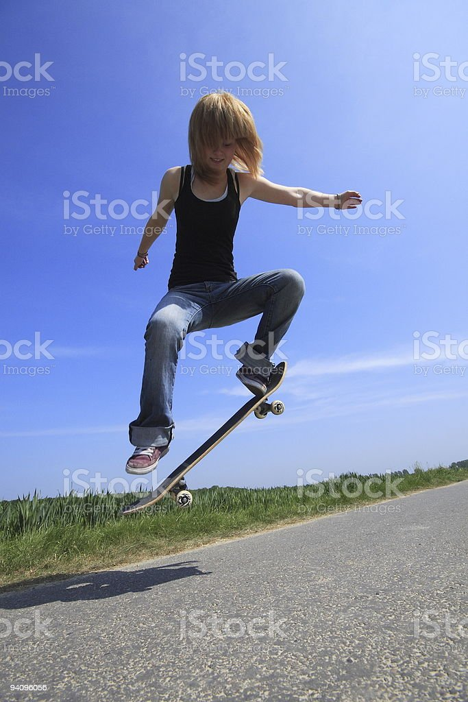 Young girl jump with her skateboard stock photo