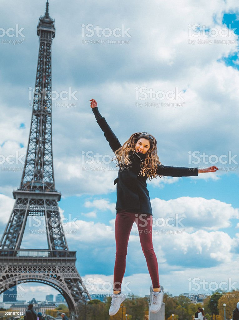 Young girl jumping against Tour Eiffel stock photo