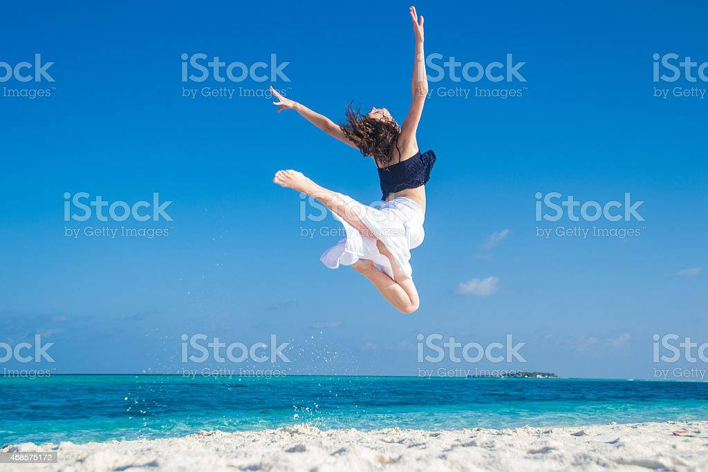Young girl jumping at tropical beach stock photo